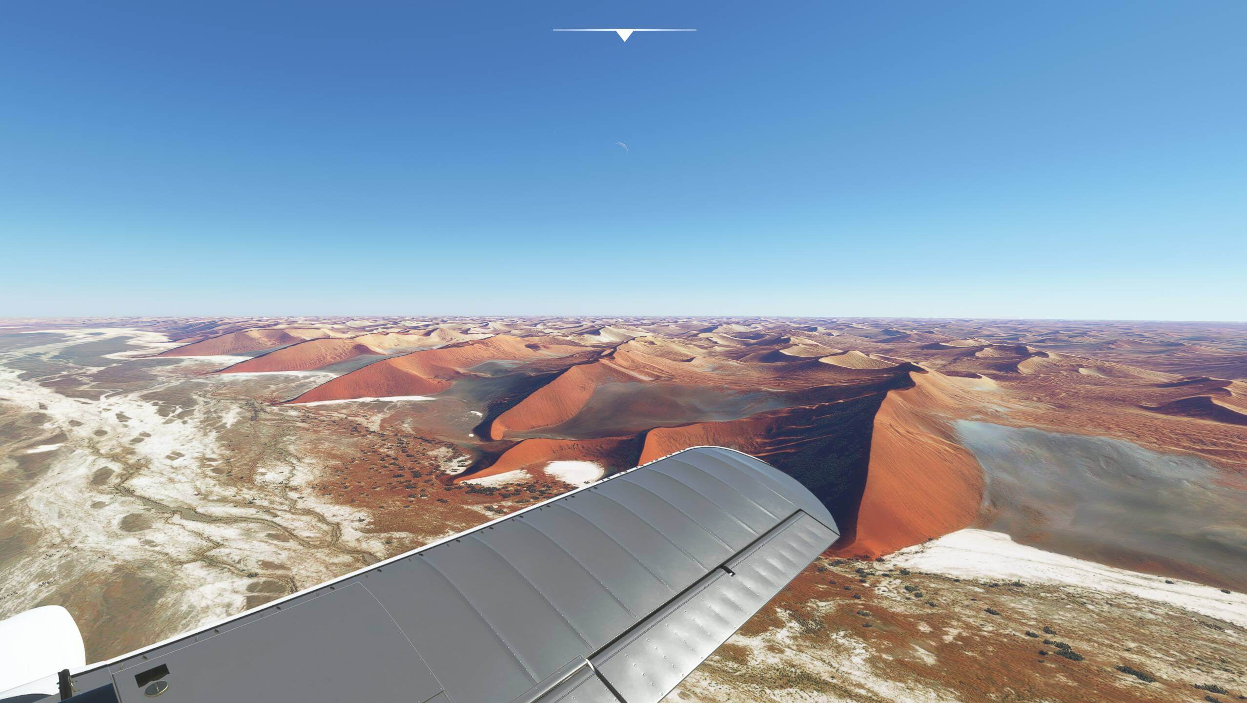 Plane wing view over desert dunes