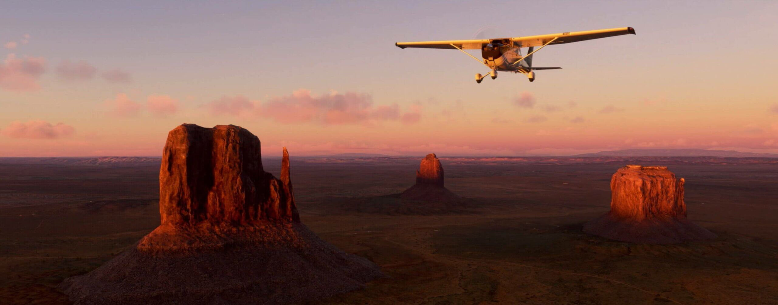 A plane flies over monument valley